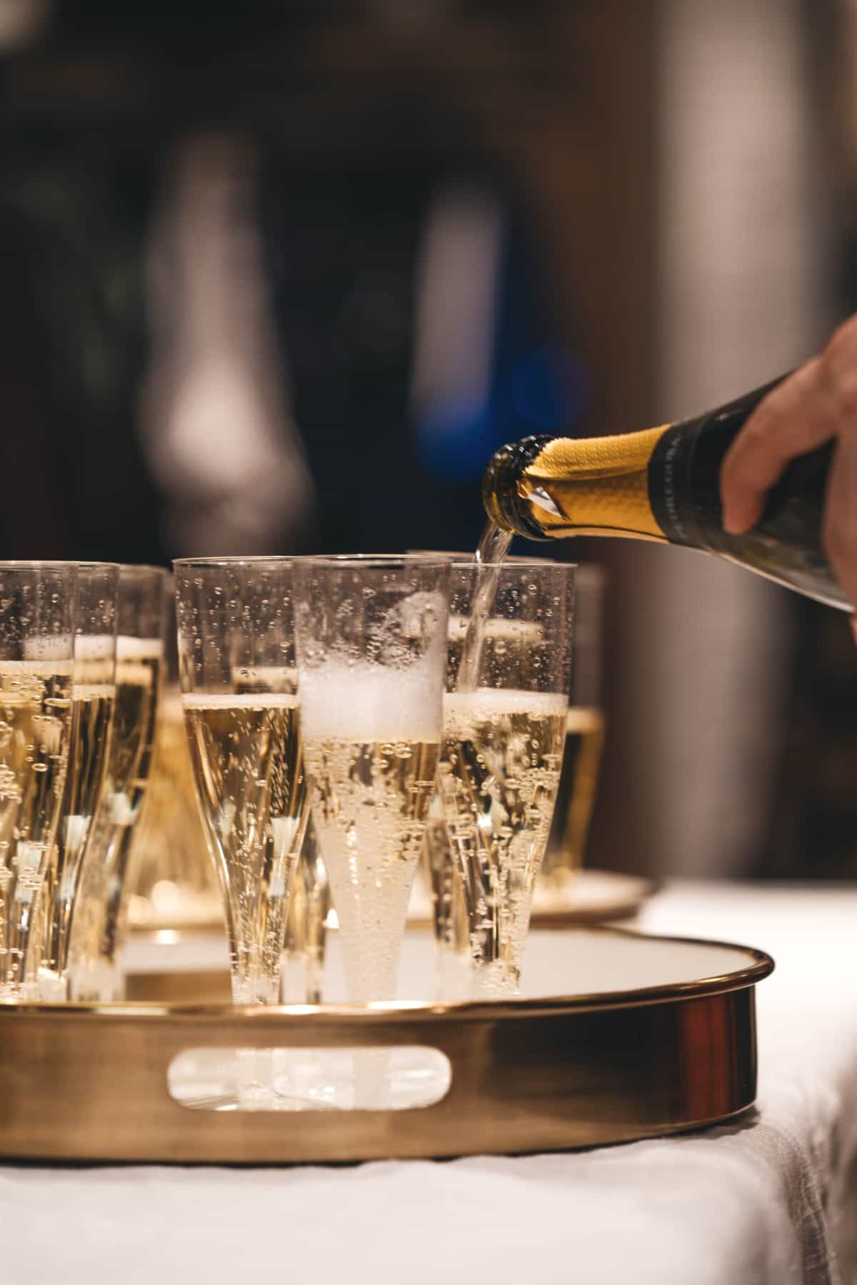 champagne being poured from a bottle into glasses